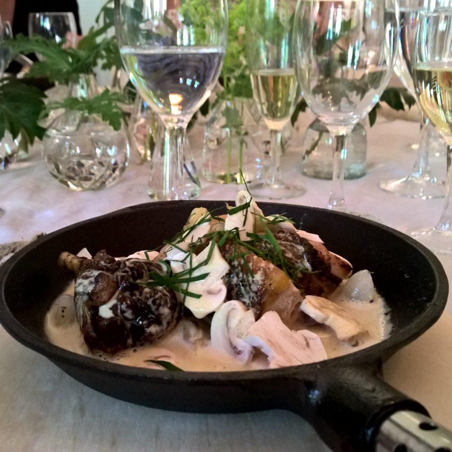 Coq au Vin blanc serverad tjusigt i gjutjärnspanna på Franska Residenset