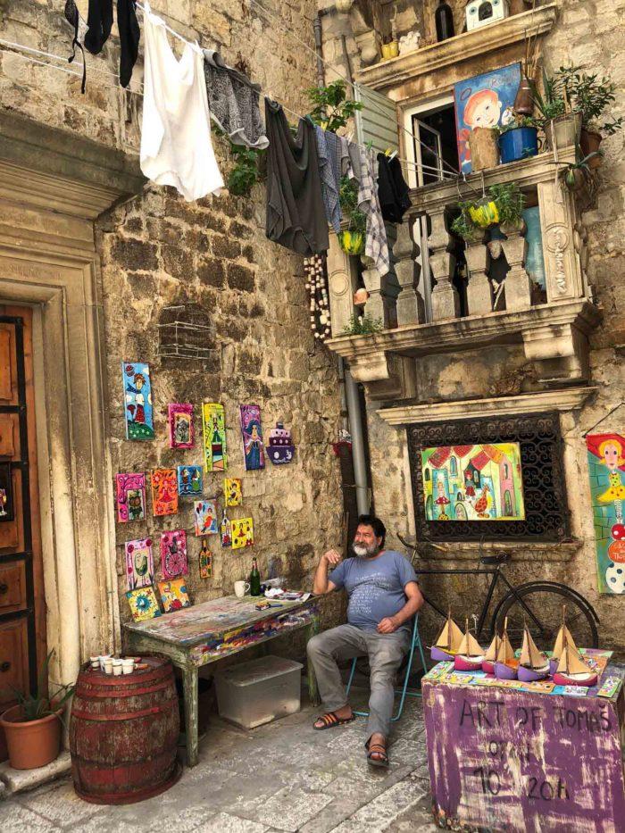 En konstnär i Trogirs charmiga gränder.