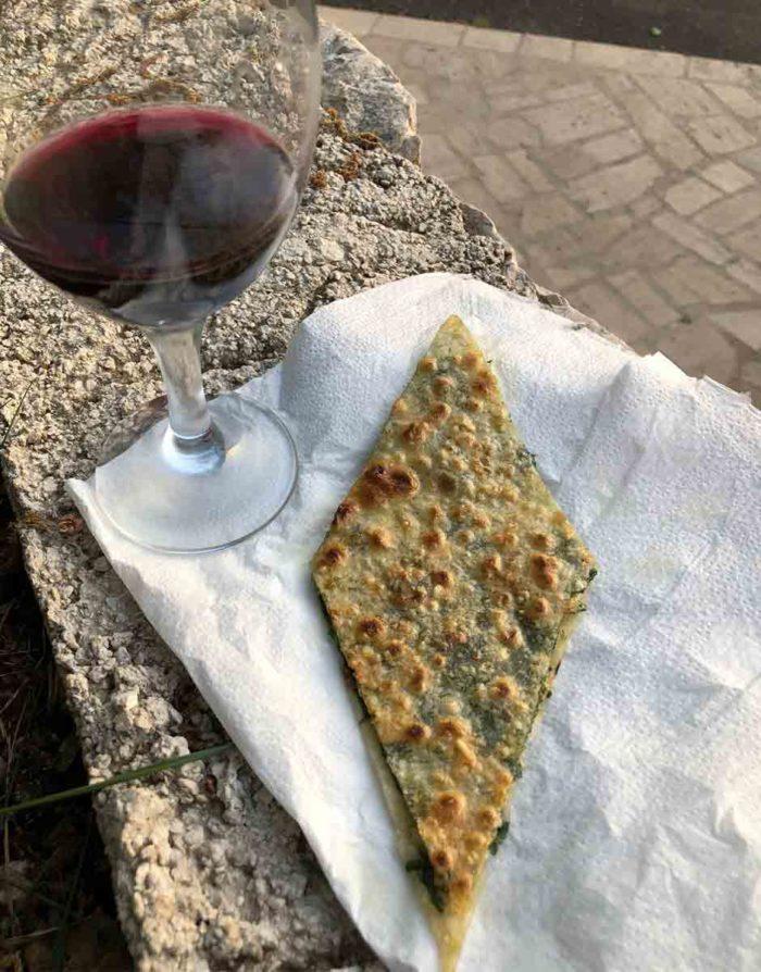 Den nygräddade brödet penslas med vitlökisolja och skärs i kantiga bitar. Det smakar riktigt gott till ett glas vin.