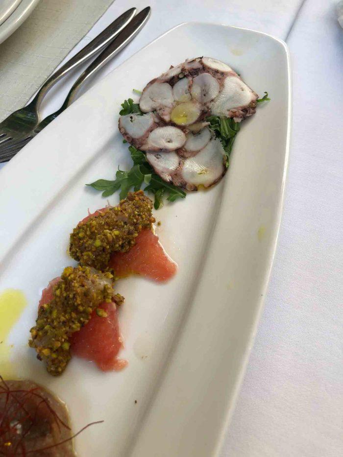 Aptitretare på restaurang Calebotta i Trogir. Tunt skivade bläckfiskterrinen och grapefruktfiléer med små råa fiskbitar täckta av mandelcrunch.